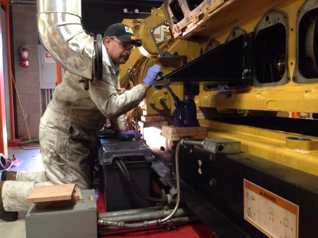 Jeff Borello a mechanic inspecting a piece of heavy machinery