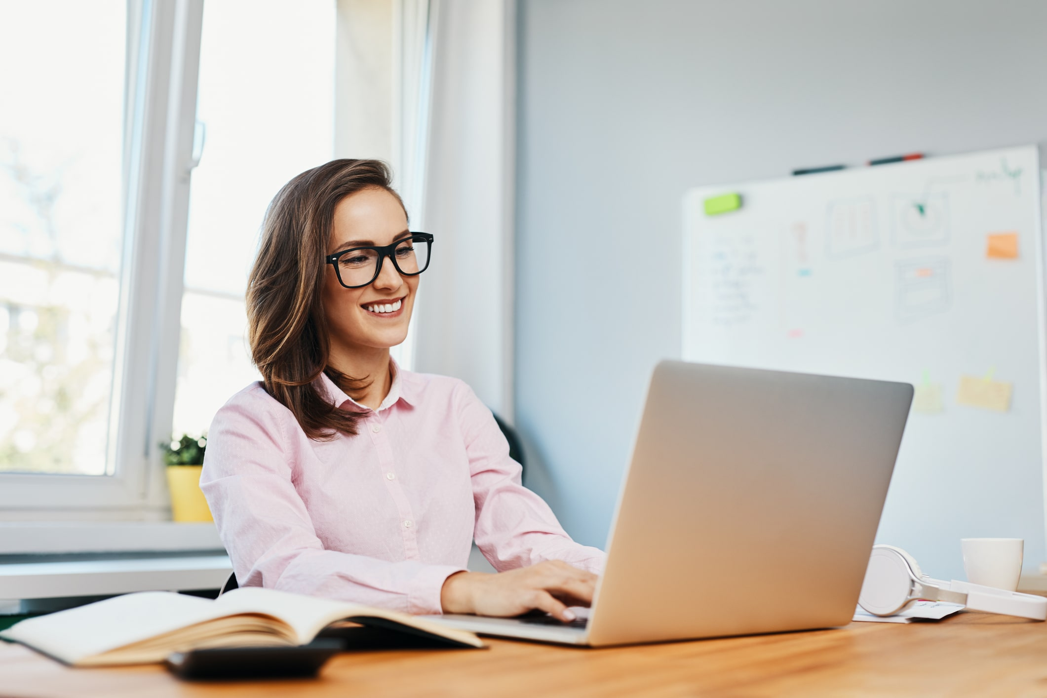 A smiling woman working on her laptop in an office.